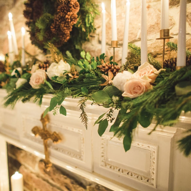 evergreen and roses drapping over fireplace with a gold cross