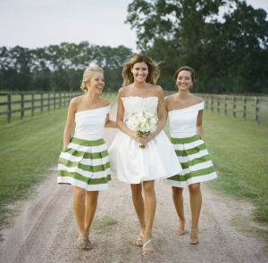 bride in short gown walking with bridesmaids in white and green striped dresses
