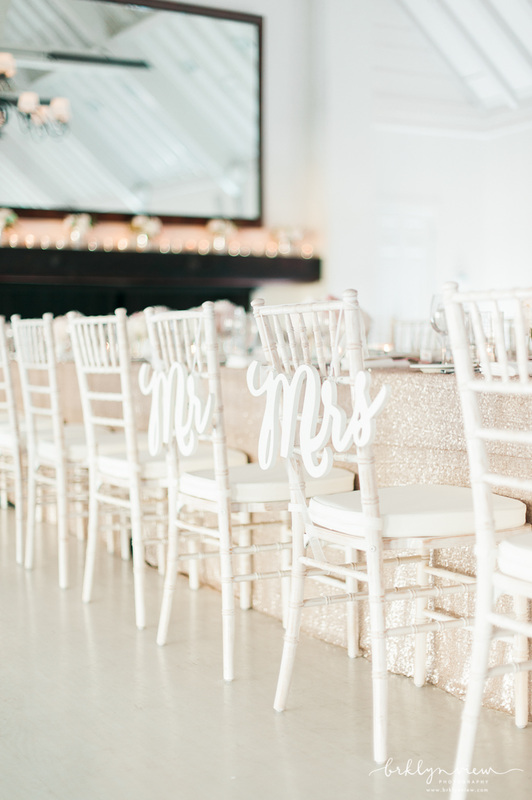 white reception chairs and white Mr. and Mrs. signs