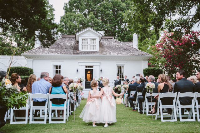 flowers girls walking down aisle towards white southern mansion