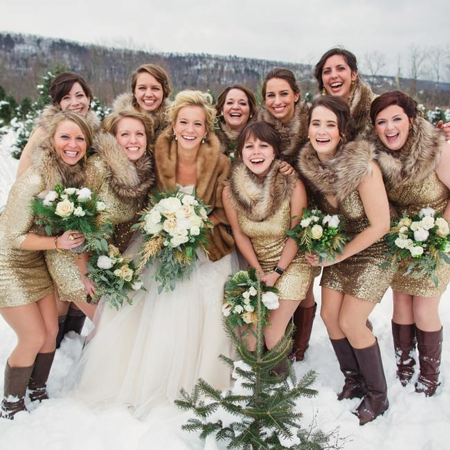 bride standing with bridesmaids in short glittery dresses and fur shawls in the snow