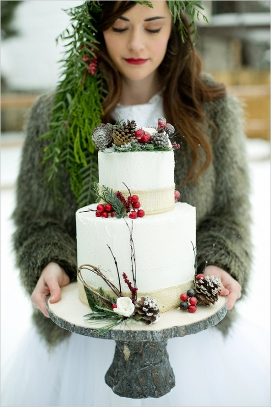 bride in fur coat in the snow holding wedding cake