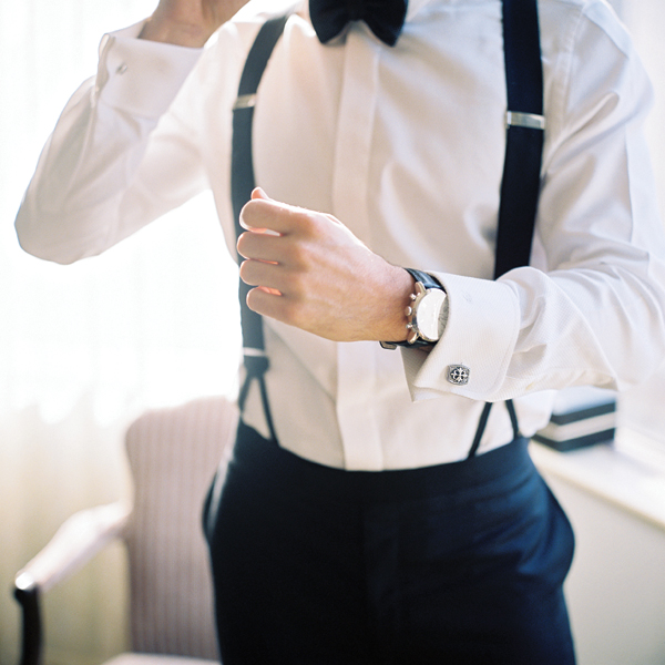 groom in black suspenders getting ready