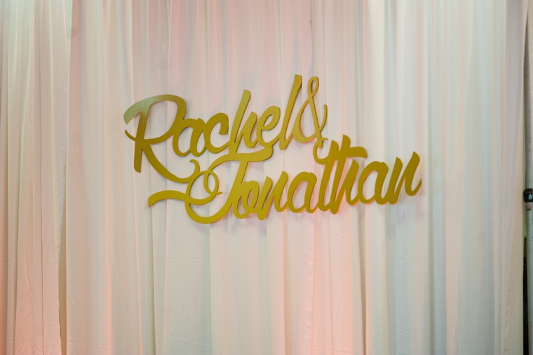 gold wedding names against curtains with uplights