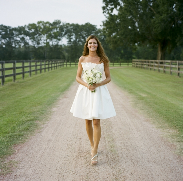 short white brides dress holding white bouquet on riding pathway