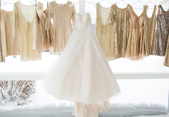 wedding dress hanging with glittery bridesmaid dresses