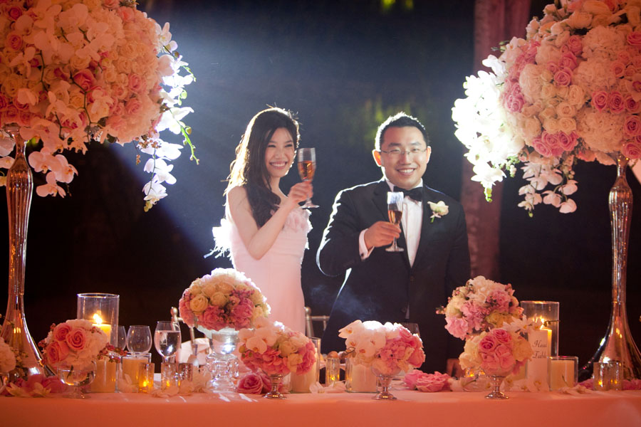 bride and groom toasting at sweetheart table with lavish flowers surrounding them