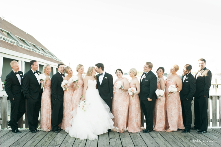 bridal party on dock posing while bride and groom kiss