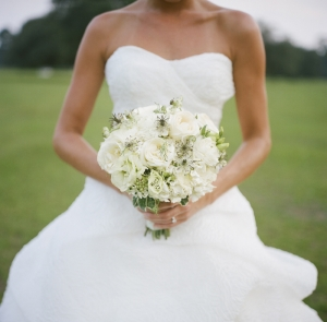 bride holding white flowers on polo field