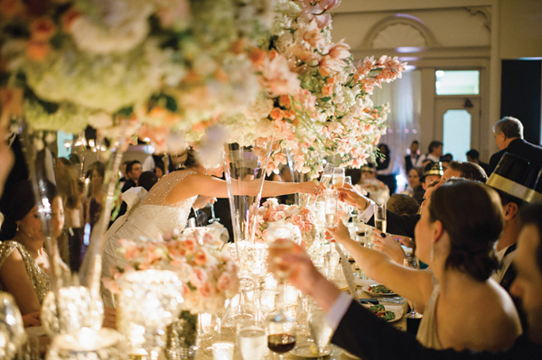 elaborate wedding florals with high and low centerpieces and couples toasting