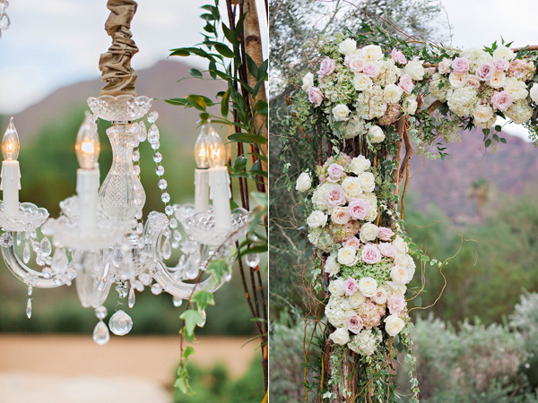 hydrangeas and roses decorated on a wedding arbor with chandeliers