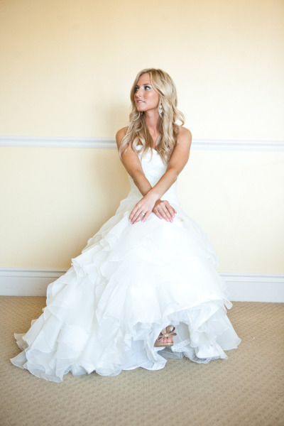 bride sitting on chair showing Valentin wedding shoes