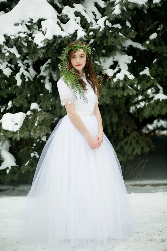 bride posing in the snow with evergreen crown