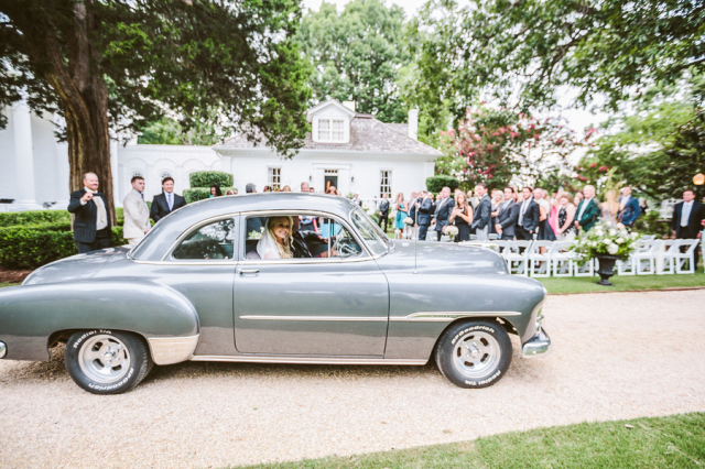 vintage silver car with bride and groom