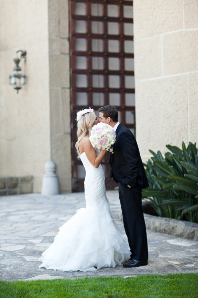 bride and groom kissing with brides bouquet covering the kiss