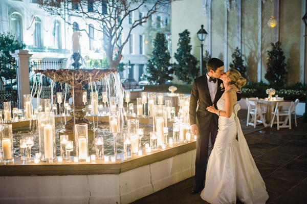 bride and groom kissing outside with hundreds of candles surrounding a fountain