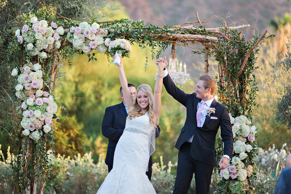 bride and groom celebrating after kiss, wedding arbor covered in flowers