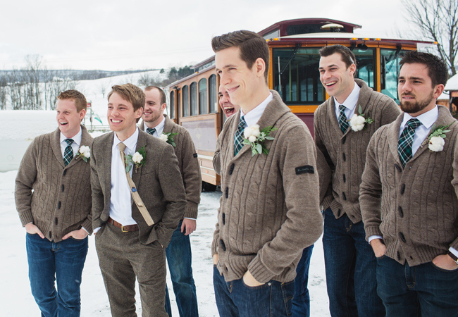 groomsmen in sweaters and plaid ties standing in the snow