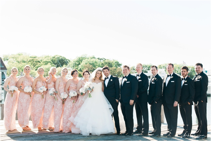 bride and groom with bridal party in tuxes and long peach dresses