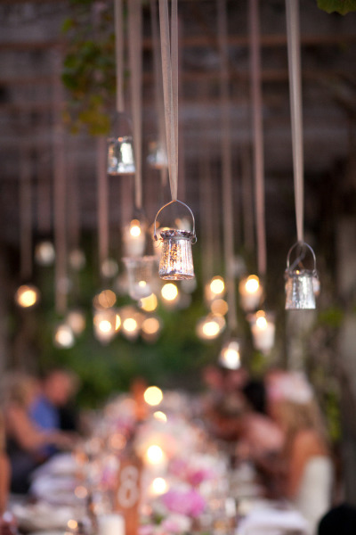 hanging candles and lights glistening over wedding table