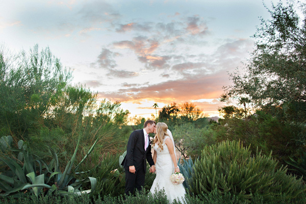 bride and groom kissing with desert sunset in background