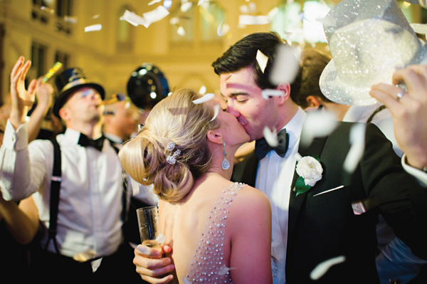 bride and groom kiss at midnight during new years eve wedding and confetti in the air