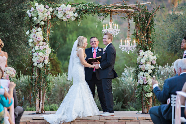 wedding arbor with branches roses and hydreangeas and chandeliers