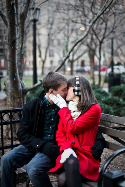 cuple kissing in the winter on Chicago bench