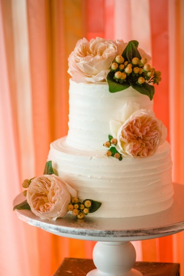 white wedding cake with peonies and pink streamers