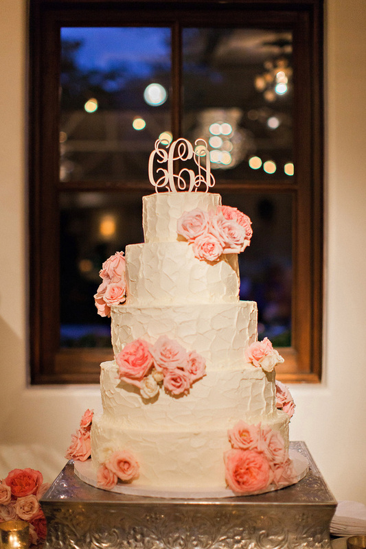 white wedding cake with pink flowers and monogrammed cake topper