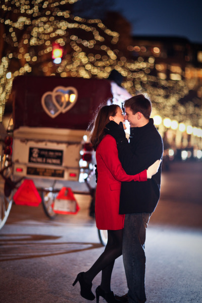 Christmas couple infatuated with each other in front of carriage