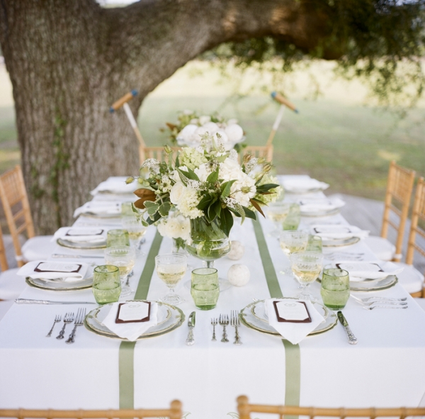 white and green outdoor table setting with table runner, bouquets of flowers and delicate place settings