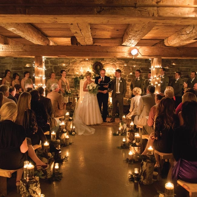 wedding ceremony in session in cabin with lots of candles and Christmas lights