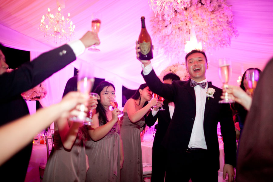 groomsmen toasting standing guests with bottle of dom