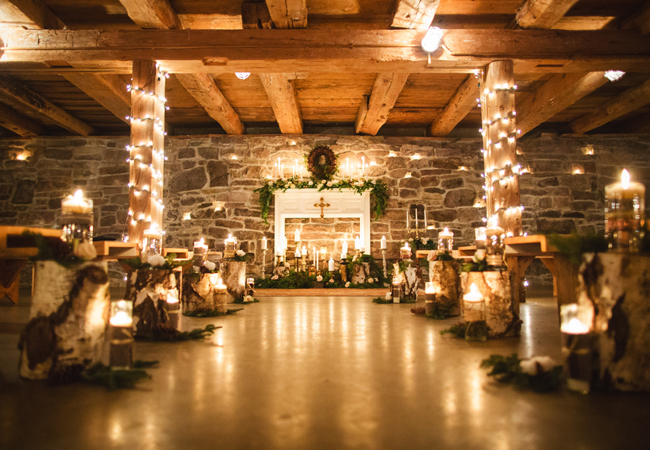 wedding ceremony aisle in rustic cabin light up with lots of candles and Christmas lights