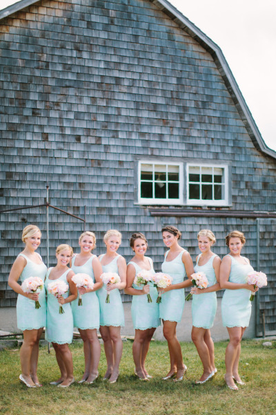 bridesmaids in light blue short bridesmaid dresses holding peach and pink bouquets