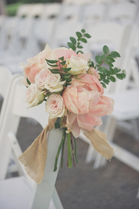 pink roses and peonies ties on wedding aisle chairs