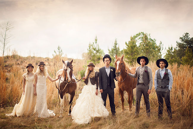 vintage wedding with wedding party all wearing hats holding two horses