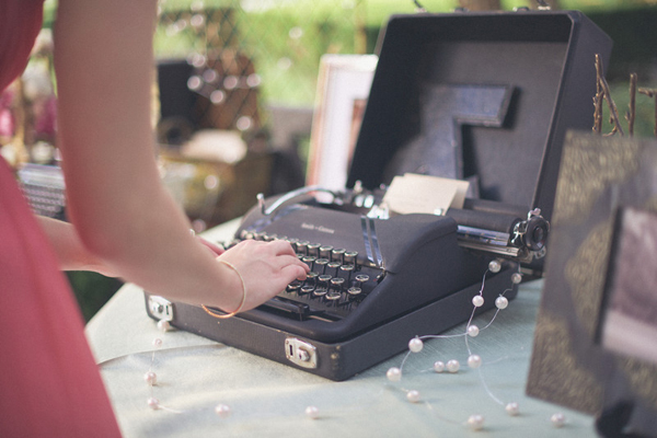 wedding guest typing note on old typewriter for the newlyweds