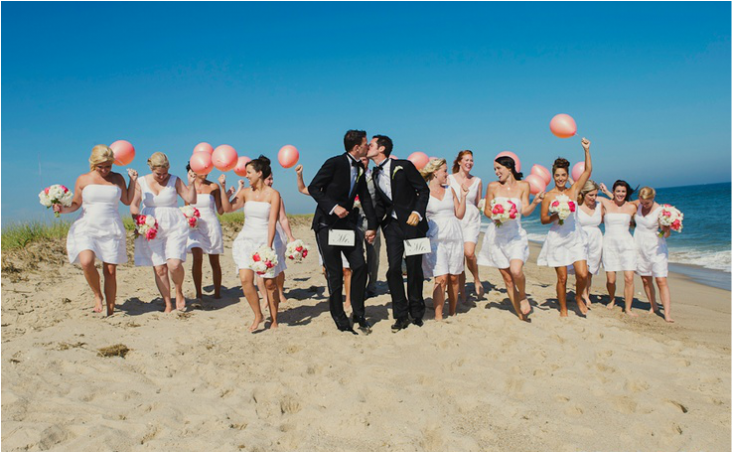 grooms kissing and bridesmaids in short light blue dresses on the beach holing pink balloons