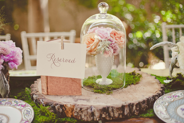 pink and orange wedding flowers in a white vase on a tree slice and colorful china