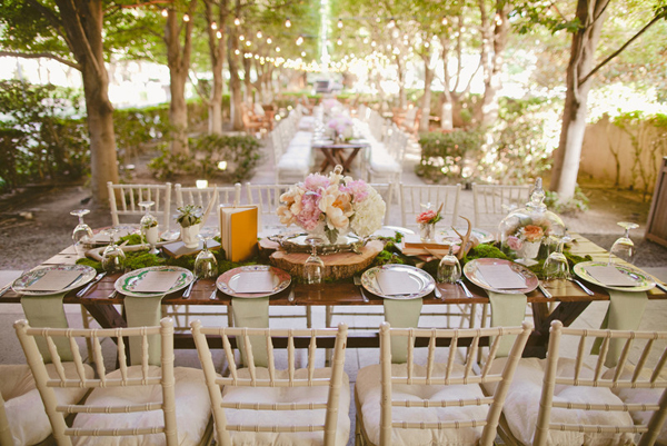 outdoor wedding reception tables decorated with moss, tree slices, books, pink and white flowers and hanging edison lighting