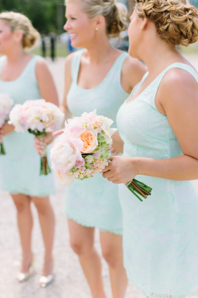 bridesmaids in light blue dresses carrying peach and pink peonies and hydrangeas