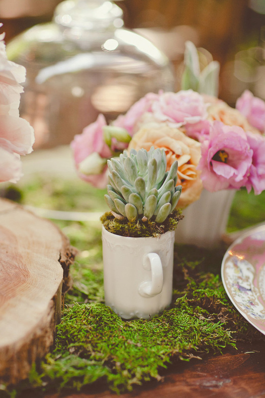 table decorated with moss, tree stump, pink and orange flowers and potted white coffee mugs