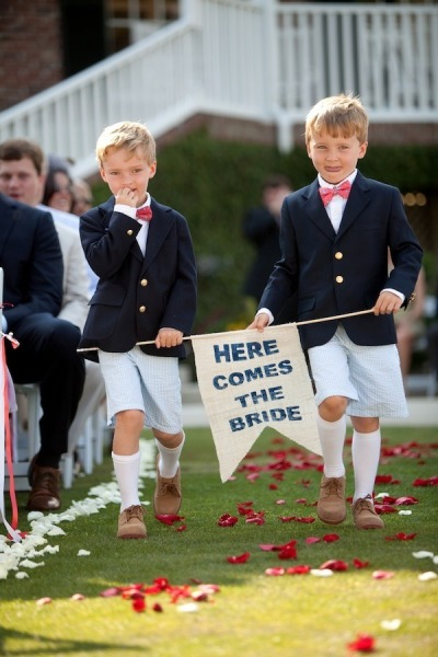 boys in navy suits walking down the aisle carrying here comes the bride sign