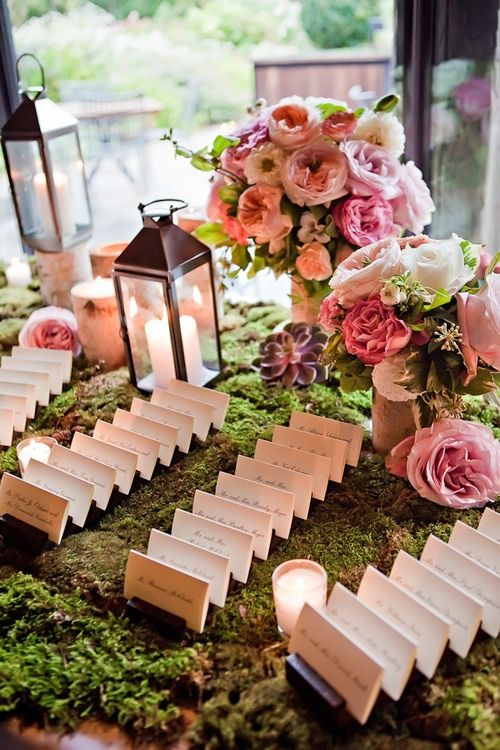 pink wedding flowers on escort card table with moss