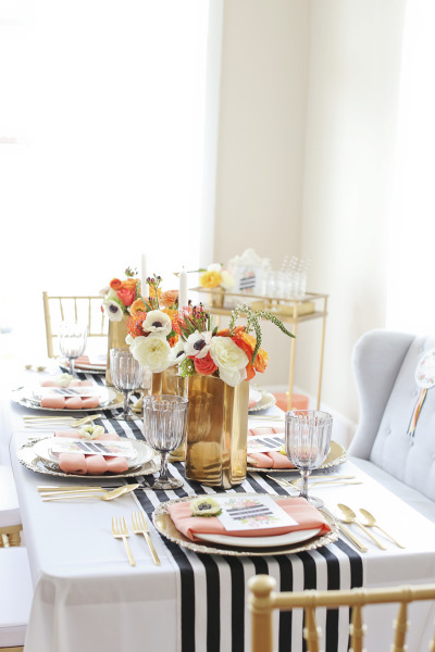 styled engagement party table with coral, white and navy florals and place settings with gold touches