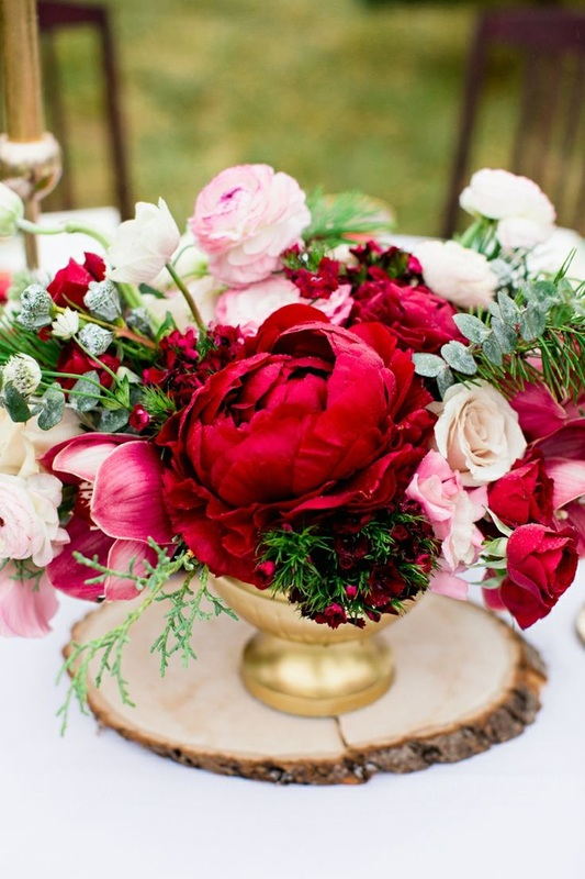 red and white wedding reception flowers in gold vase