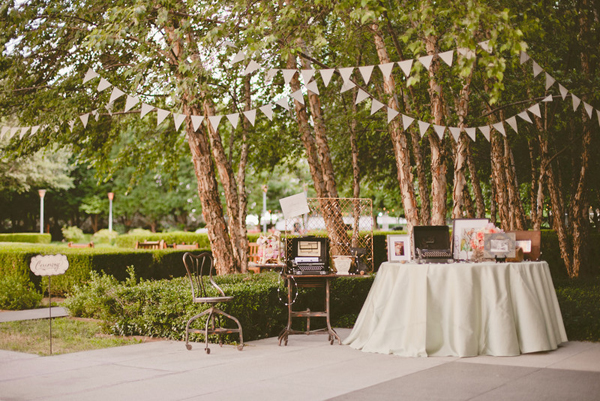 outdoor wedding table with guest book and well wishes table and hanging burlap triangles