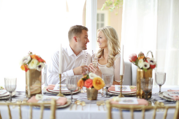 couple looking at each other and toasting at styled table